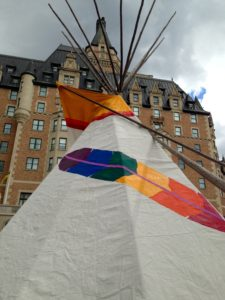 A tipi with a rainbow feather painted on it, in front of Saskatoon's Bessborough hotel
