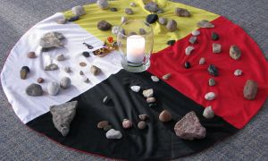 A medicine wheel cloth, with a candle in the centre and stones placed on the cloth.