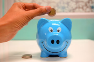 A blue piggy bank with a hand dropping a coin in.