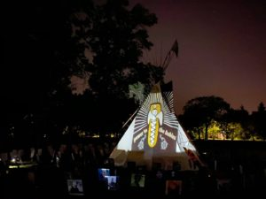 A tipi at night, surrounded by photos of those lost to suicide. Projected on the tipi is an image of a baby in a cradleboard and the words Power to Our Babies.