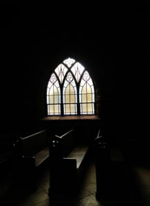 A stained glass window casting light on a pew.