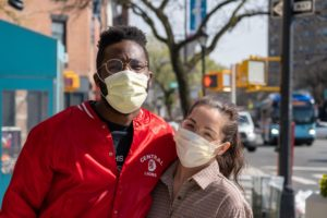Two people wearing masks and smiling, with a streetscape in the background.