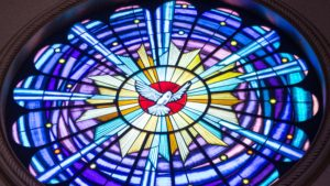 A stained glass blue and purple ircle with a starburst and dove in the center.