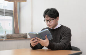 Rev Lee is seen reading a bible, seated at a table, wearing glasses and a dark sweater.
