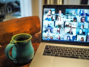 A laptop with people's faces in the usual online meeting squares. A blue pottery mug is next to the keyboard.