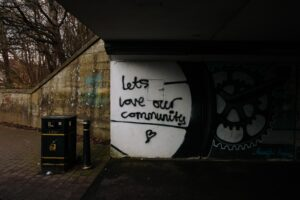 """Graffiti on a concrete wall reading """"let's love our community""""."""