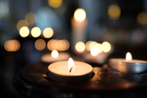 A lit tealight in focus, with many more behind it, fading into the background.